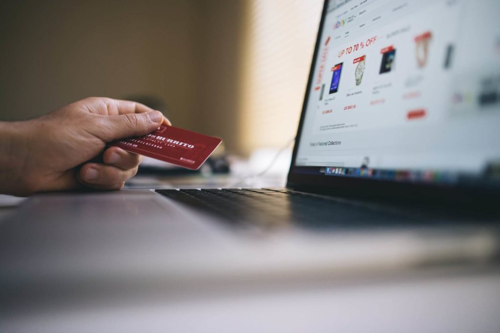 Man holding credit card in front of the laptop