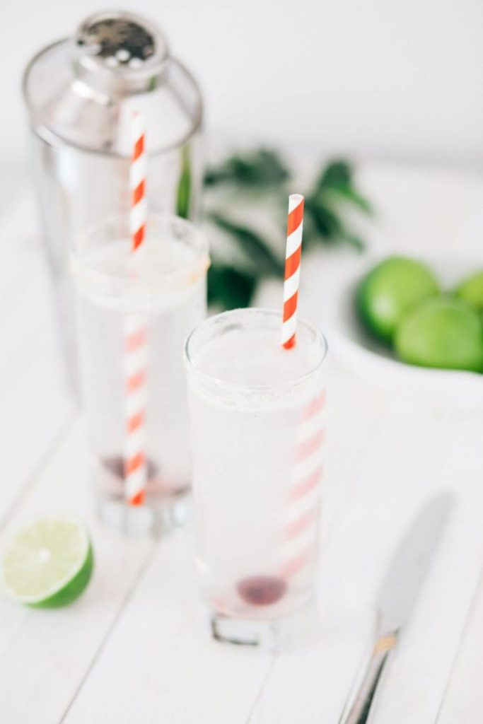Two glass of detox ice tea with red and white straws
