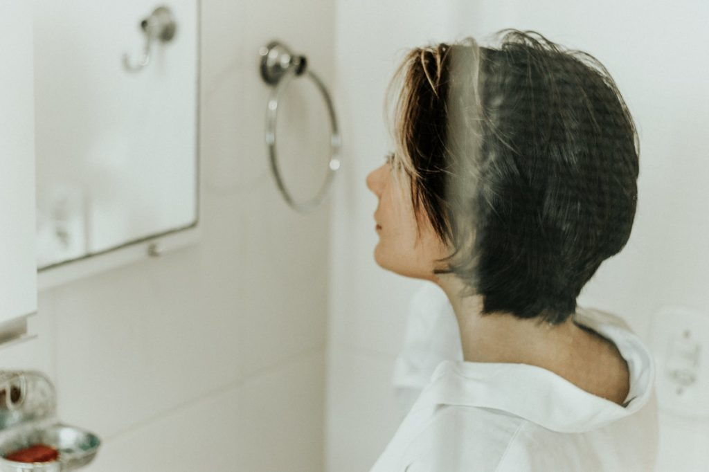 Woman with Brown Hair Looking into a Bathroom Mirror