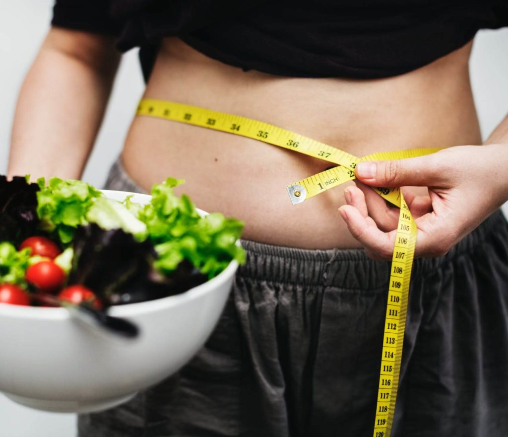Woman Holding Salad in Bowl with Measuring tape around her belly