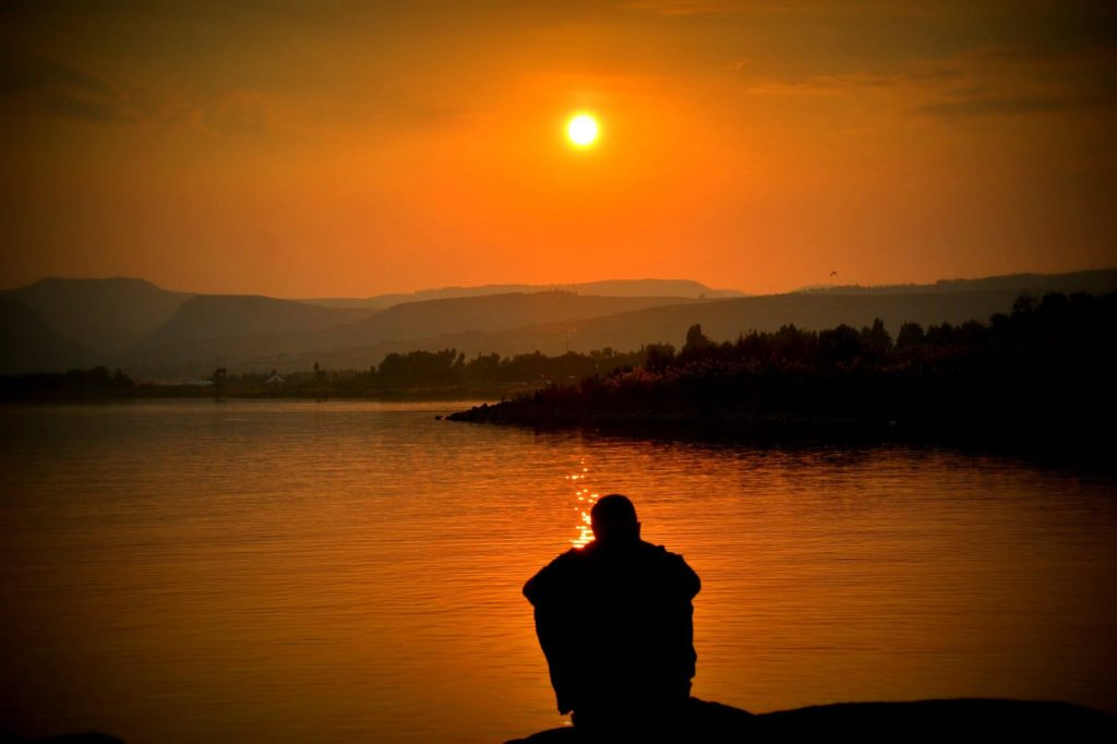 Man watching the sunrise over a lake